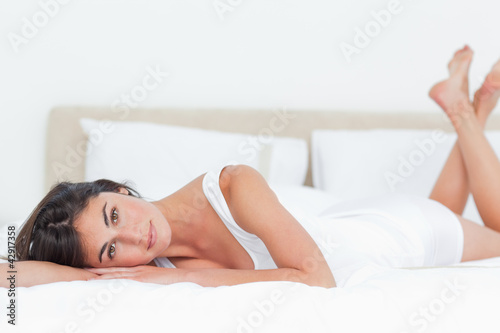Portrait of a beautiful brunette in her bed