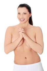 Beautiful naked woman covering breast and smiling.