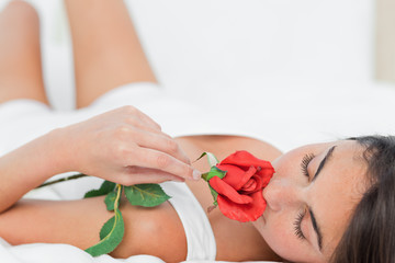 Brunette lying on her back while smelling a rose