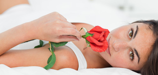Portrait of a brunette lying on her back while smelling a rose