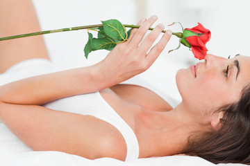 Woman lying on her back while smelling a rose
