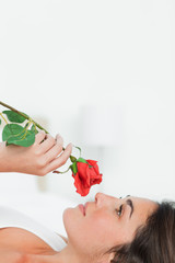 Close-up of a brunette lying on her back while smelling a rose