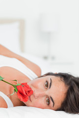 Close-up of a lovely girl lying on her back while smelling a rose