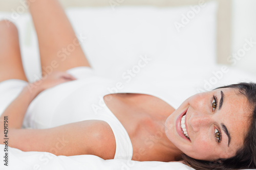 Portrait of a smiling brunette lying on her back