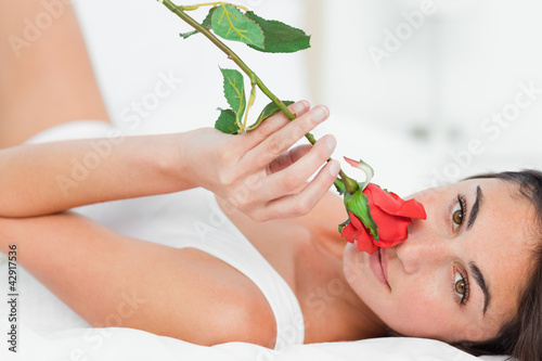 Portrait of a woman lying on her back while smelling a rose