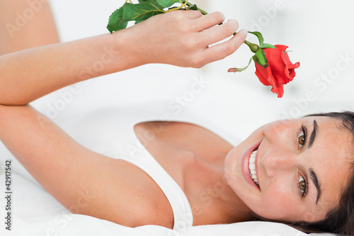 Portrait of a brunette lying on her back while holding a rose