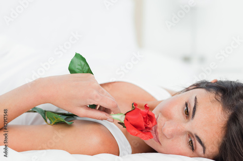 Beauty lying on her back while smelling a rose