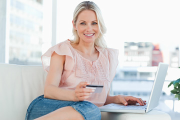 Portrait of a blonde buying online with a laptop