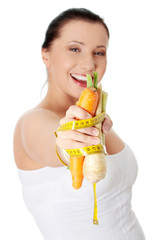 Smiling young woman holding vegetables.