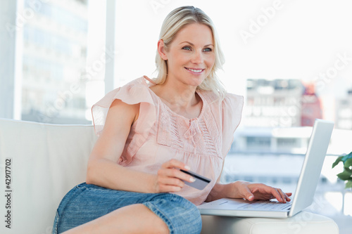 Smiling blonde buying online with a laptop