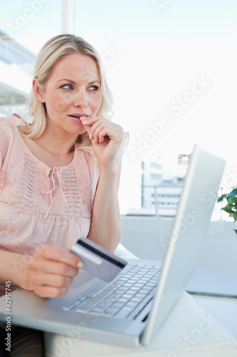 Close-up of a blonde thinking to shop online