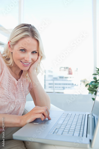 Portrait of a smiling blonde on a laptop