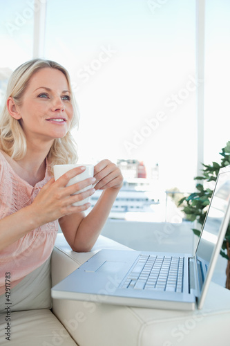 Smiling blonde on a laptop with a coffee