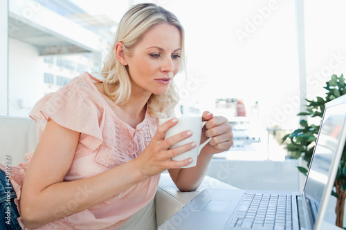 Blonde on a laptop with a tea