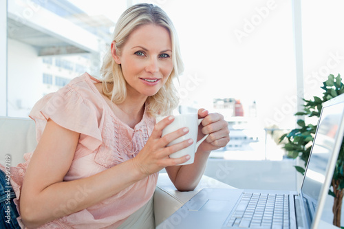 Portrait of a blonde on a laptop with a coffee
