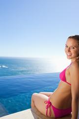 Smiling woman sitting on swimming pool edge