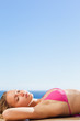 Woman enjoying sunny day lying on the swimming pool edge