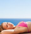 Woman relaxing in the sun lying on the pool edge