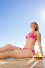 Woman enjoying the sun sitting on the pool edge