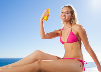 Side view of smiling woman with sunblock