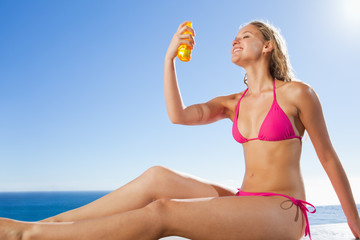 Side view of smiling woman applying sunblock