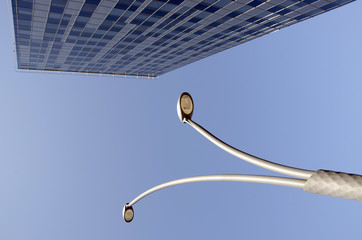 High glass building and street lights in blue sky