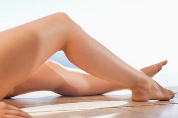 Female legs sunbathing on the pool edge