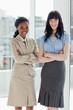 Two businesswomen standing upright with a smiling face