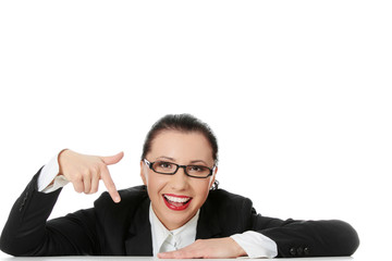 Smiling businesswoman is pointing at down.