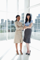 Two serious businesswomen standing upright while looking ahead