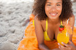 Young smiling woman lying on a beach towel while holding a fruit cocktail
