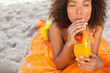 Young relaxed woman sipping a fruit cocktail while lying on the beach