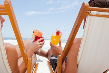 Rear view of a young couple holding their cocktails while sitting on deck chairs