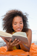 Young woman lying on the beach while reading a book in a concentrated way