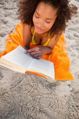 Overhead view of a young woman reading a book while lying on her beach towel