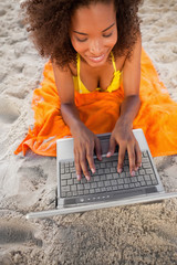 Young smiling woman using her laptop while lying on the beach