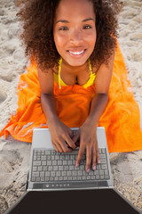 Young smiling woman looking up while using her laptop on her beach towel