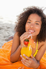Young smiling woman holding an orange cocktail while looking at the camera