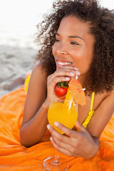 Young smiling woman looking towards the side while holding a fruit cocktail