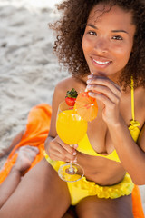 Young woman looking at the camera while drinking an exotic cocktail