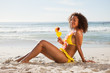Side view of a young woman sitting on the beach while holding a cocktail