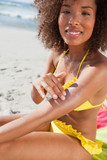 Young smiling woman sitting on the beach while applying sunscreen on her arm