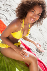 Young smiling woman sitting on her beach towel while applying sunscreen