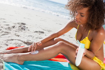 Young attractive woman attentively applying sunscreen on her leg