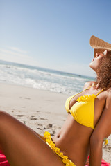 Side view of a young attractive woman sunbathing on the beach