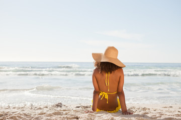Young attractive woman looking at the ocean while sunbathing