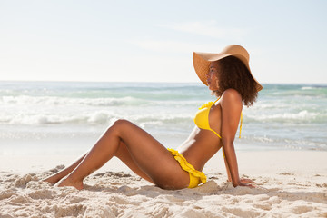Side view of a young woman sitting on the beach in beachwear