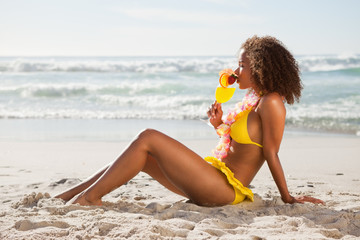 Young smiling woman drinking a fruit cocktail while sitting in front of the ocean