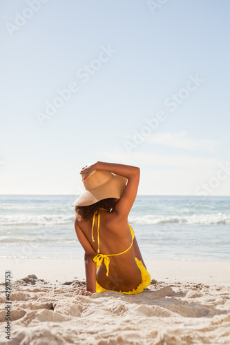 Rear view of an attractive woman holding her hat while looking at the ocean