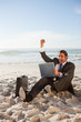 Successful businessman sitting on the beach while smiling
